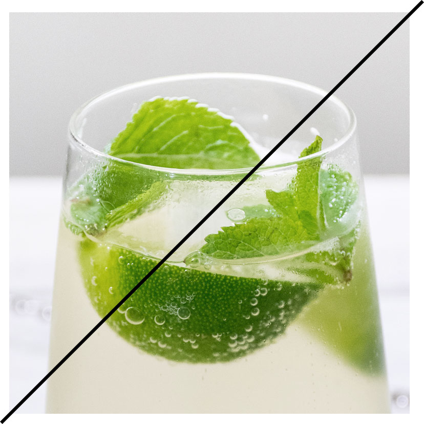 A glass filled with a drink, slice of lime and mint.