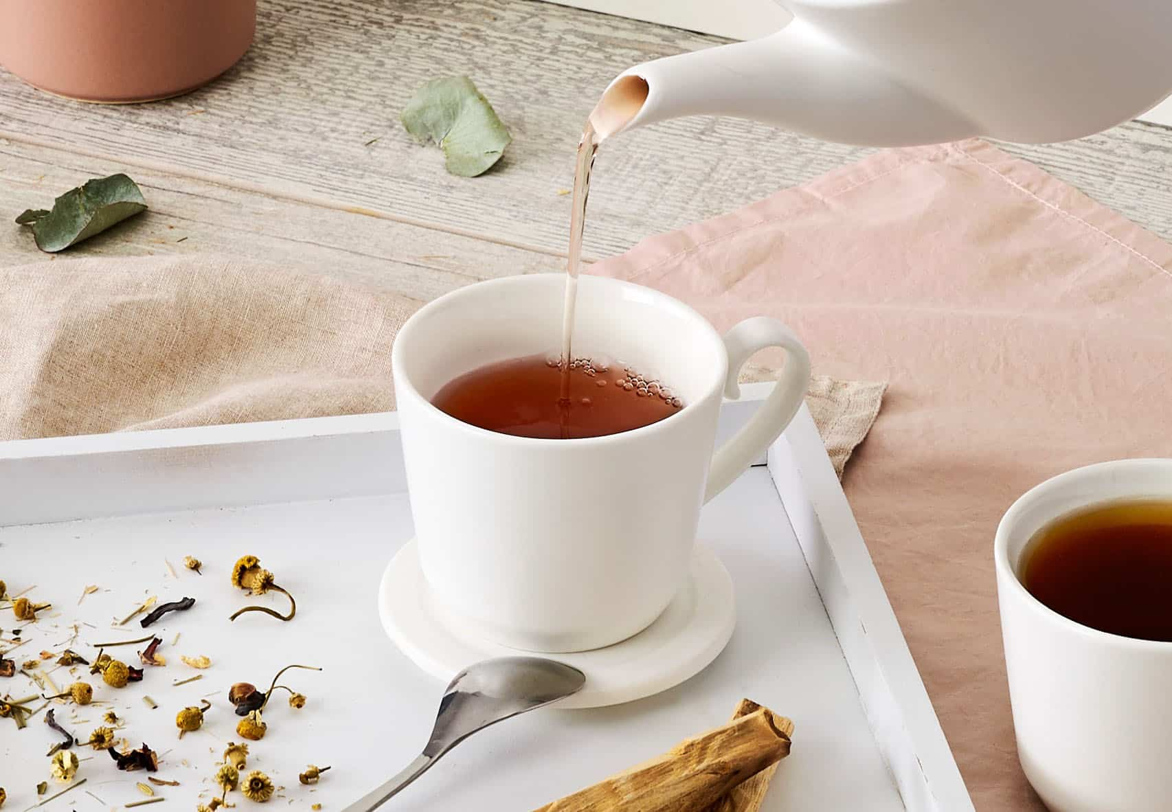 Tea poured in a white ceramic teacup placed on a tray and various neutral linens.
