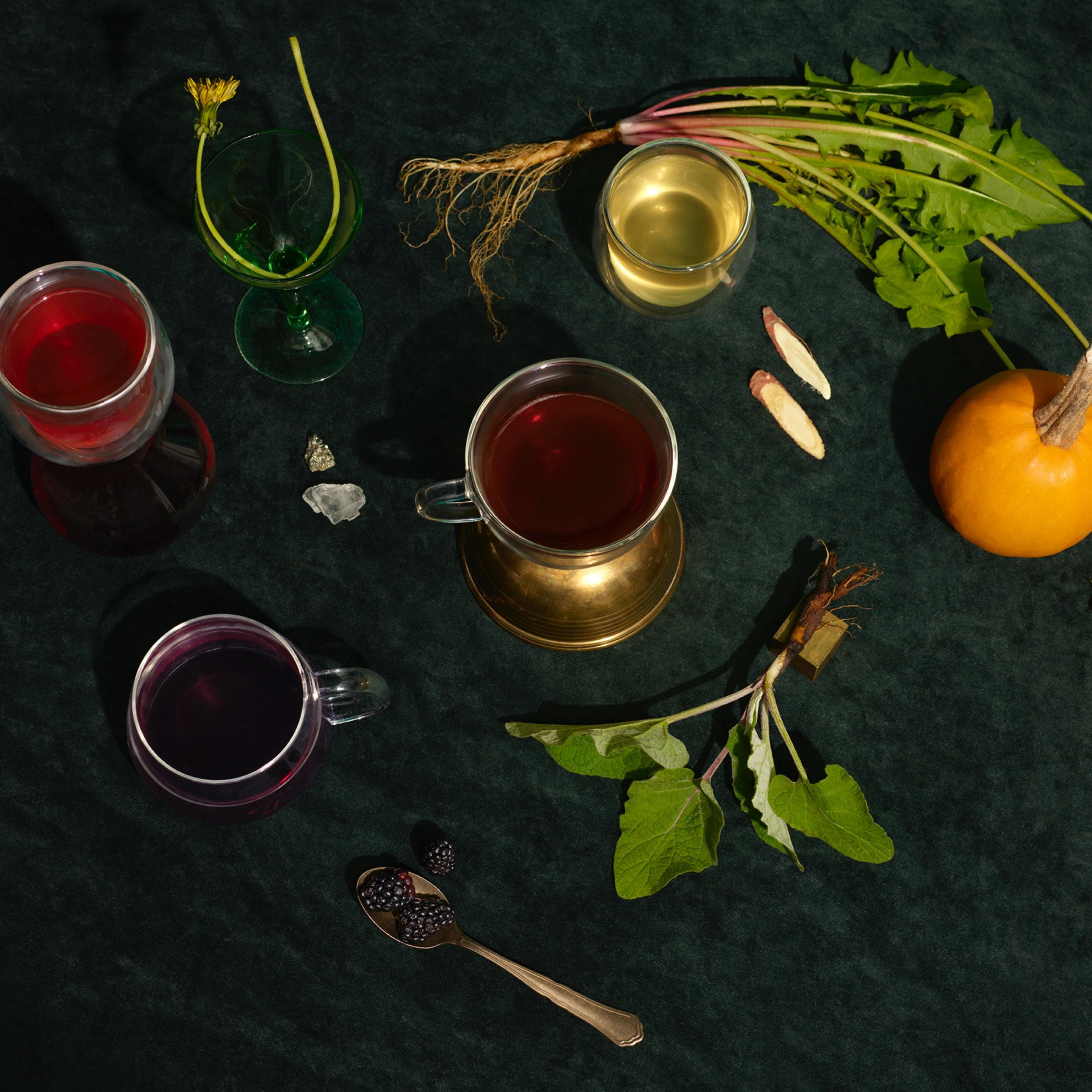 Quatre tasses en verre remplies de thés naturels contenant des ingrédients mieux-être traditionnels : bardane, racine de pissenlit, mûres.