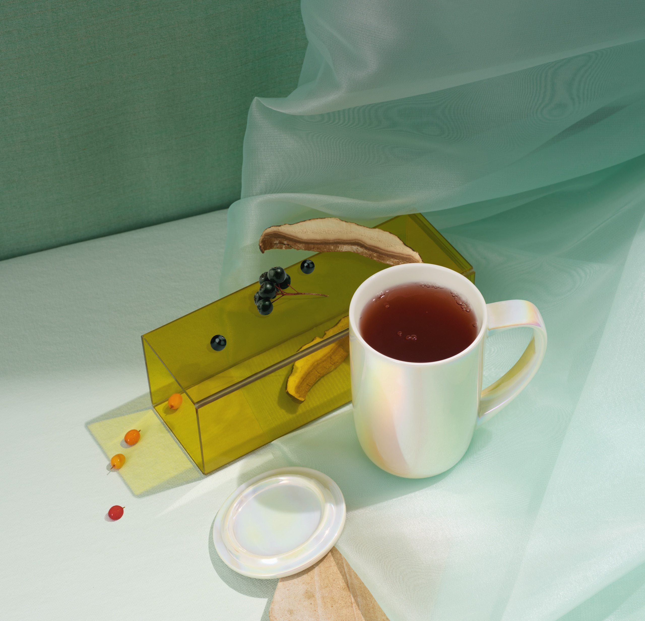 Nordic Mug filled with Reishi Recharge tea next to its raw ingredients.