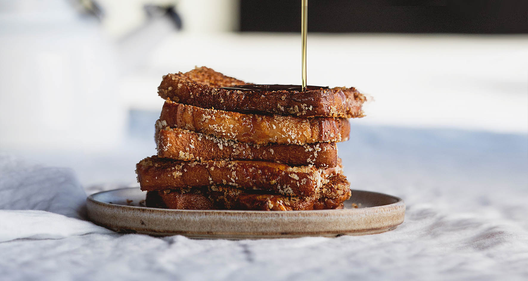 A close up shot of a stack of French toast with maple syrup drizzling on top.