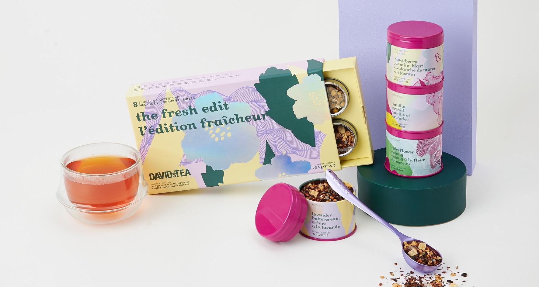 Ensemble-cadeau avec 8 thés en feuilles, boîtes à motif floral avec thé, cuillère violette, tasse en verre transparent avec thé.
