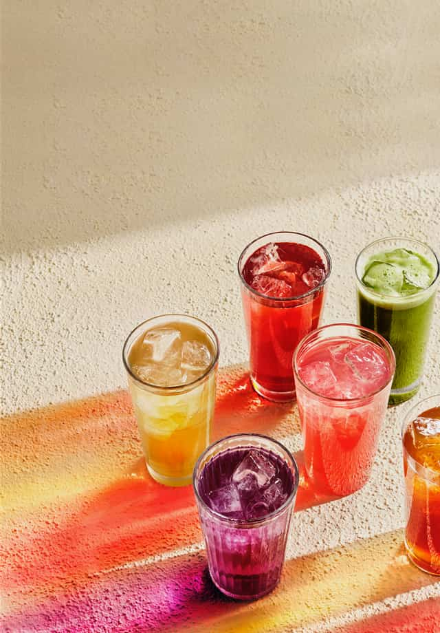 Seven glasses filled with various colourful iced teas emanating their colourful shadows.