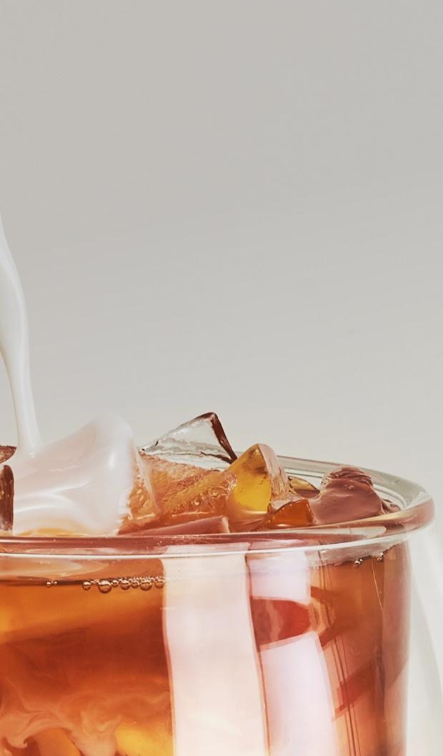 Lait versé dans une tasse 18 oz en verre double paroi remplie de latte glacé fait avec un thé dejeuner noir.