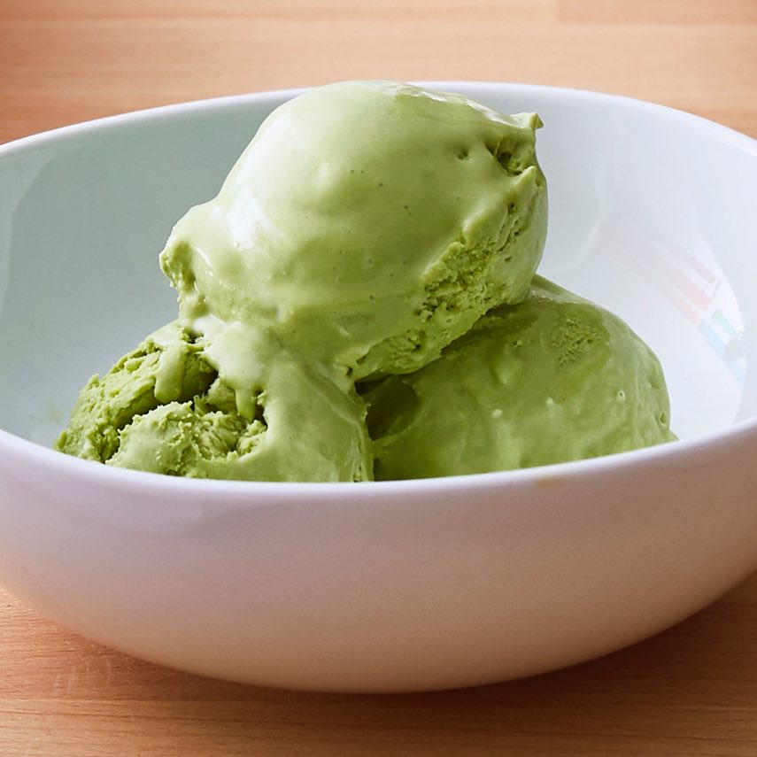 Three scoops of green soft serve ice cream made with matcha green tea powder, in white ceramic bowl.