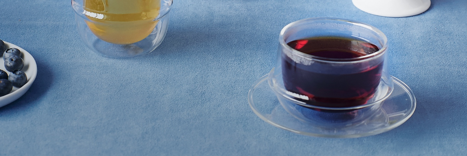 Table avec pot de confiture, scones aux bleuets, pot à thé 28 oz en céramique blanche, tasse 16 oz transparente remplie de thé.