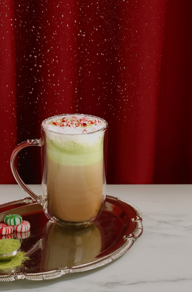 A cup filled with Candy Cane Crush with a shot of matcha  next to a glass with 5 coloured candy canes, three candies and a Perfect Spoon filled with matcha powder.