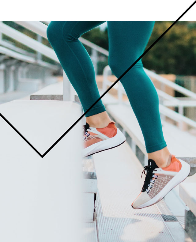 A person working out, running up stairs wearing turquoise leggings and clementine running shoes.