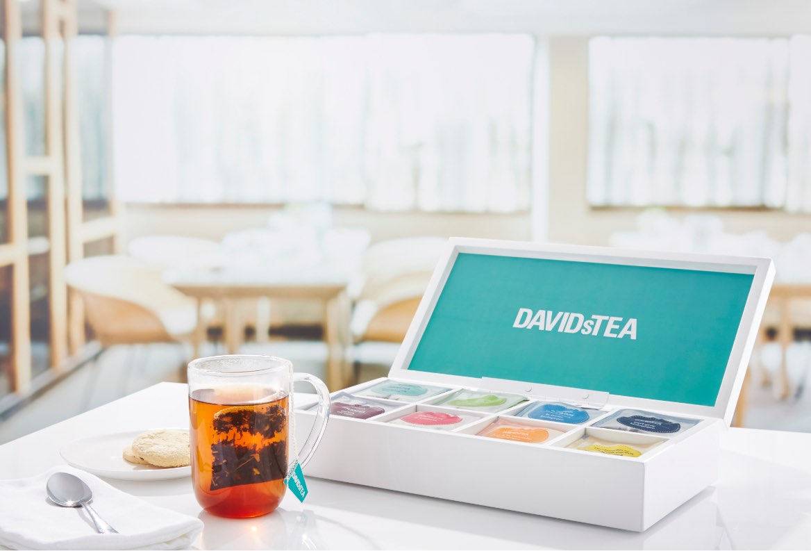 White DAVIDsTEA tea chest open on table with eight different tea types in sachets. Teabag in clear 16 oz glass mug with tea.