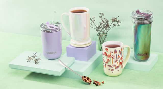 Purple 10 oz travel tumbler with straw, two 16 oz ceramic mugs filled with tea, holographic 18 oz travel tumbler with straw.