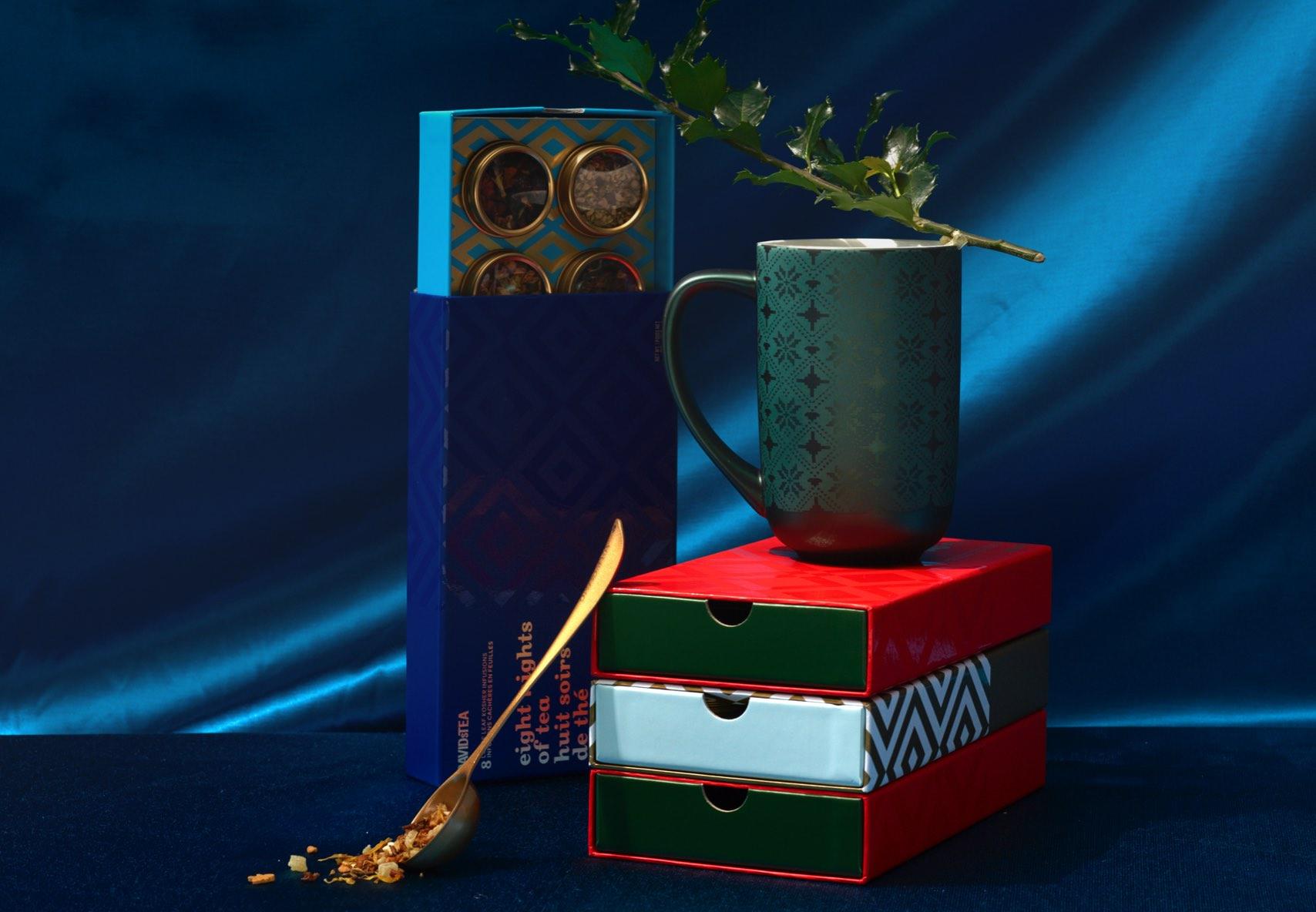 Boîtes de 8 thés empilées. Une Tasse Nordic est placée sur le dessus de trois boîtes de 8 thés, avec une Cuillère parfaite.