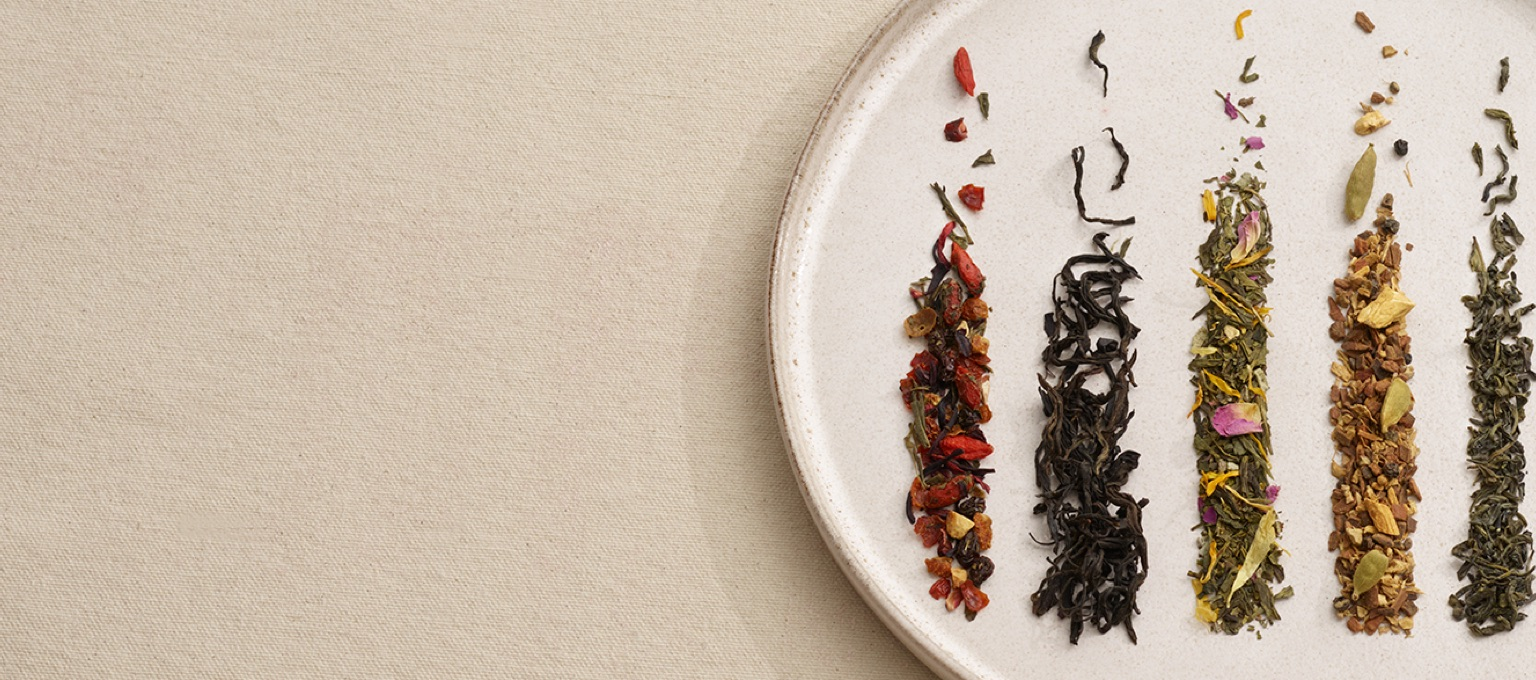 Organic loose leaf teas layed on a beige plate on a beige background.
