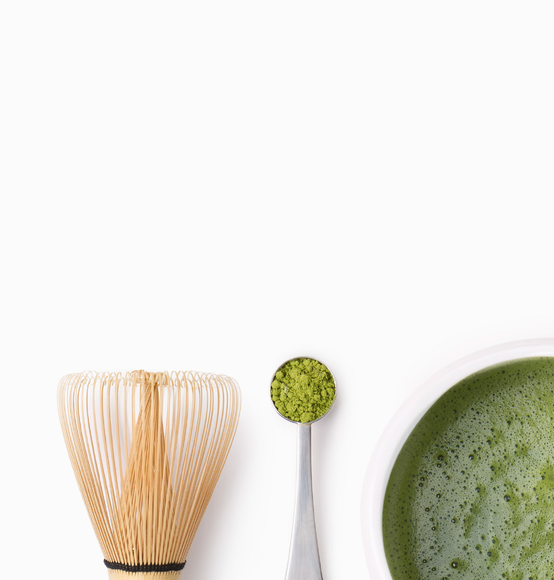 Top of matcha whisk, matcha Perfect Spoon filled with matcha and half a cup of match tea.