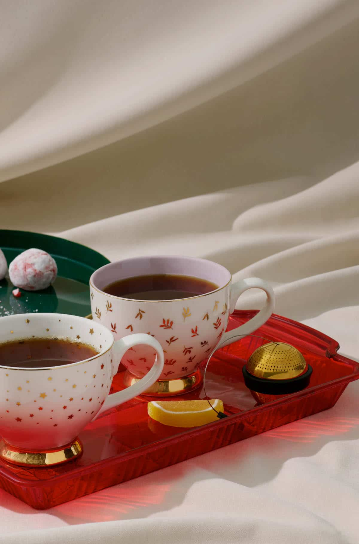 Two jolly teacup placed next to each other with a gold mesh ball and various sweet snacks next to them.
