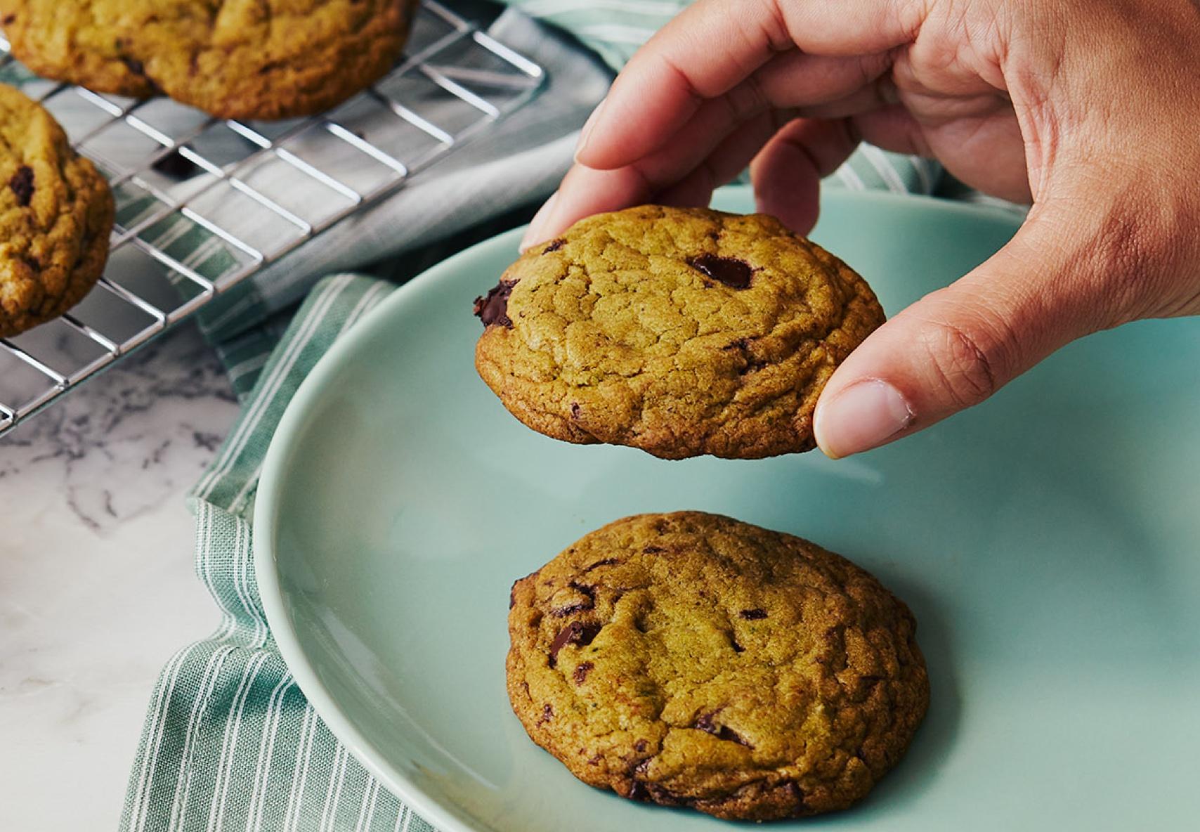 Une main s'apprête à tremper un biscuit au chocolat dans un petit verre de lait, plus de biscuits représentés à l'arrière-plan sur une grille de refroidissement.