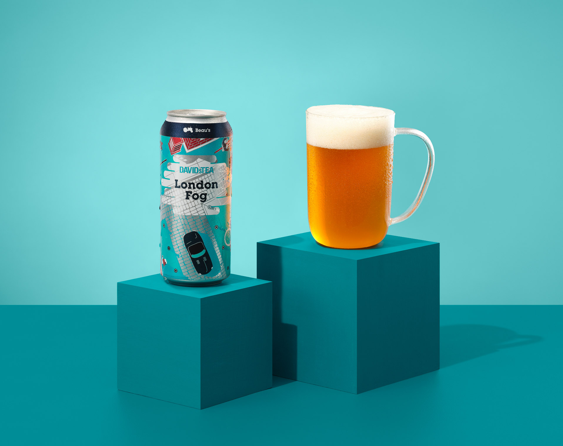 Two cans of DAVIDsTEA x Beau's London Fog (one laid horizontally on the side and the other is set on a turquoise block) with a clear mug filled with London Fog beer.