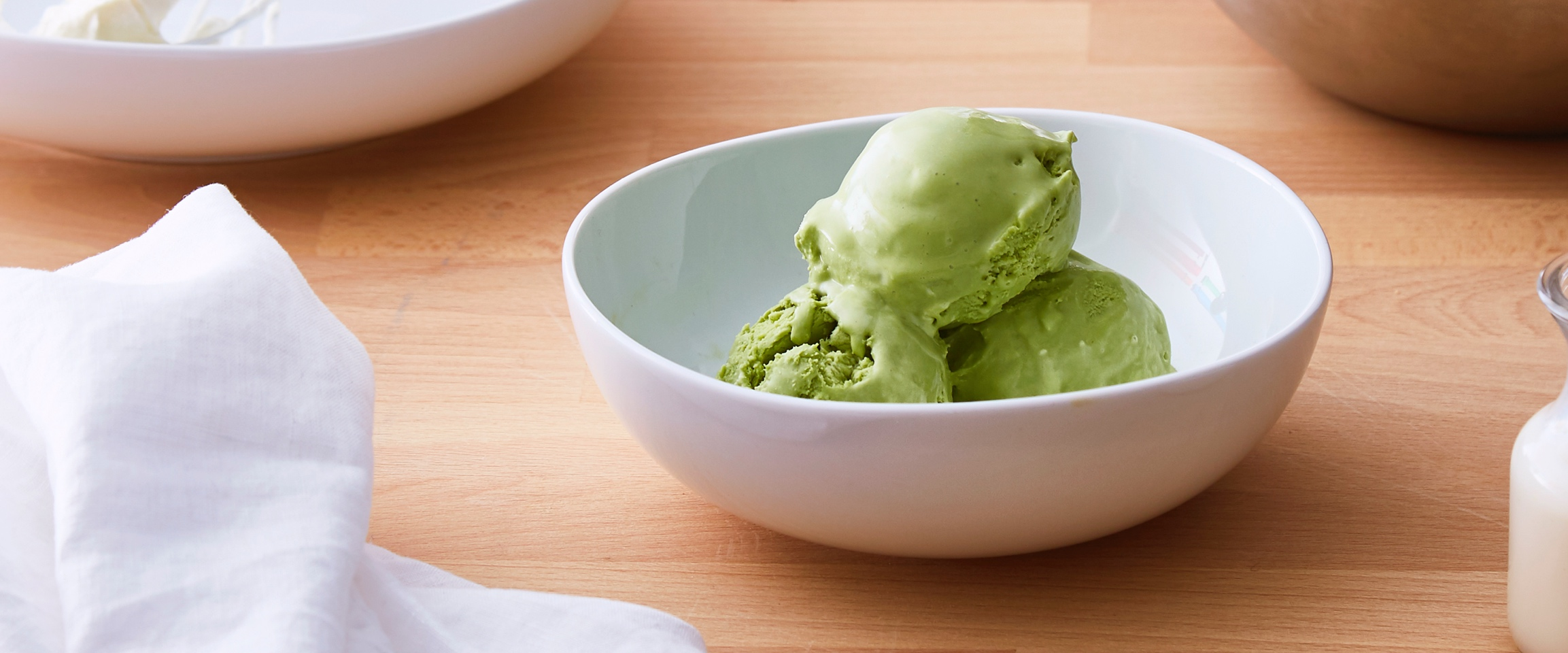 Matcha ice cream in a white bowl.