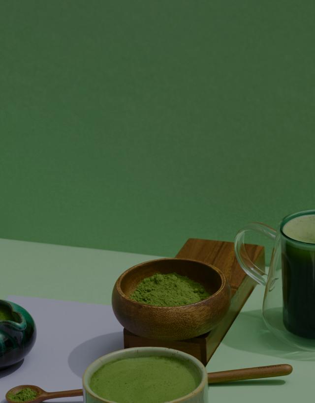 Des tasses variées remplies de matcha et de poudre matcha devant un fond vert.