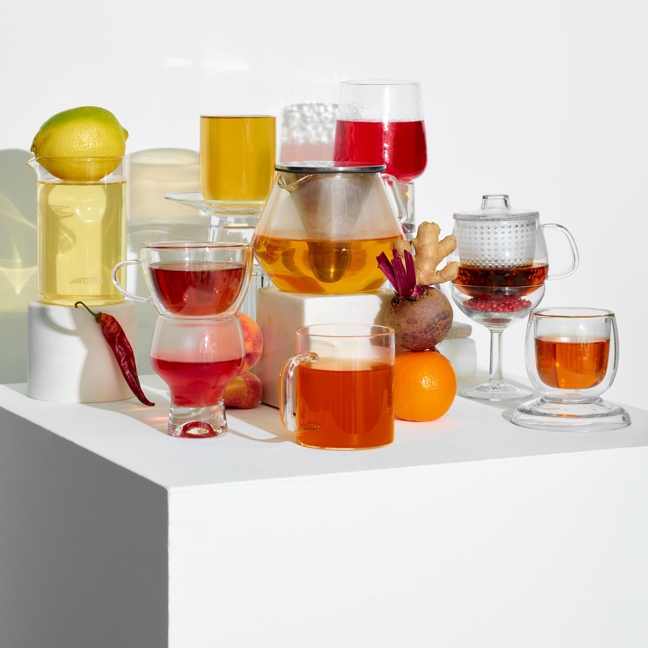 Tasses et théières en verre avec thés en feuilles glacés à base d'ingrédients naturels antirhume : citron, gingembre et chili.