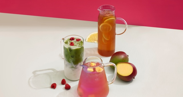 Deux pichets en verre transparent remplis de thé glacé avec tranches d'agrumes. Un pichet en verre transparent rempli de matcha latte glacé.