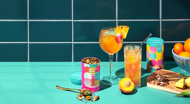 Multiple glasses filled with iced teas next to raw fruits, iconic tins & accessories.
