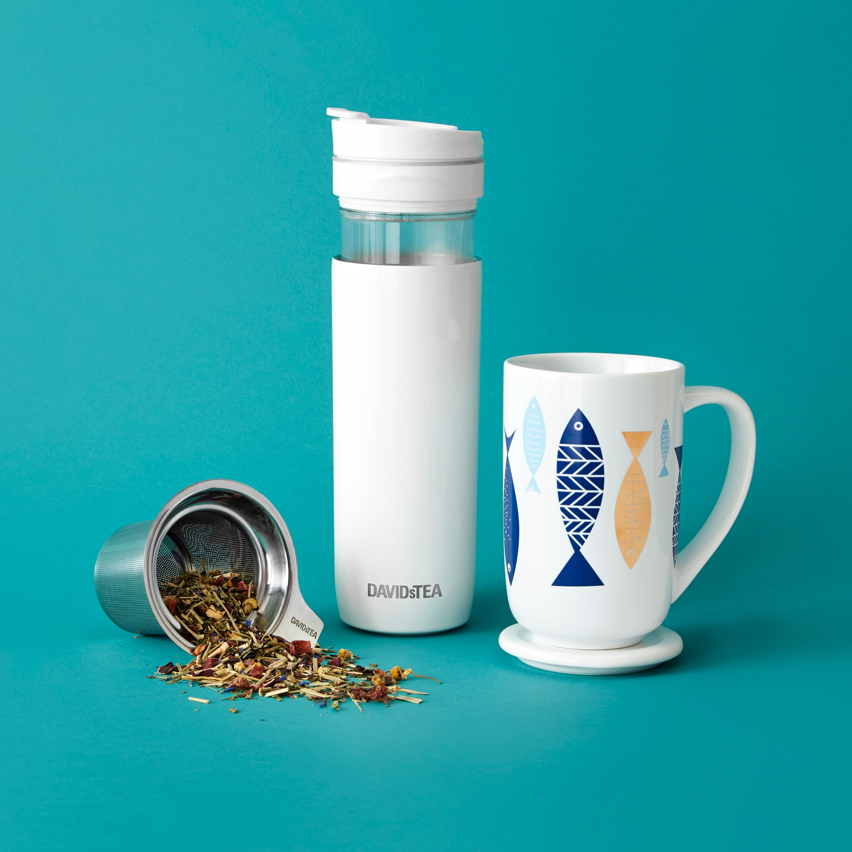 A metal infuser lies on its side, spilling over with loose leaf tea, while a white Tea Press & Fish Nordic Mug stand to the right.
