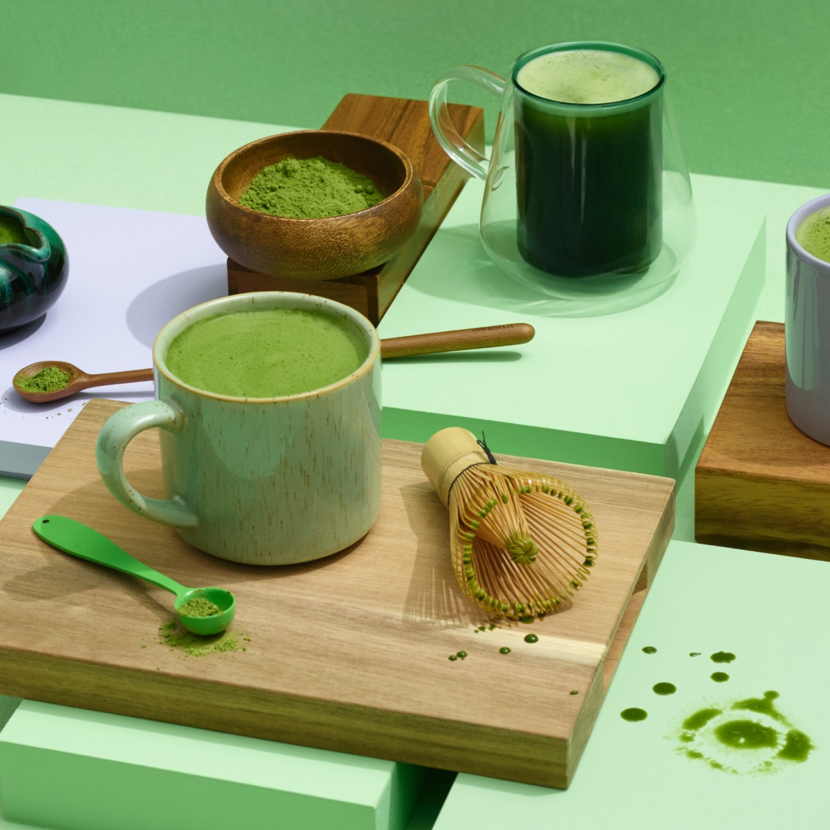 Various mugs filled with matcha and matcha powder on a gree backdrop.