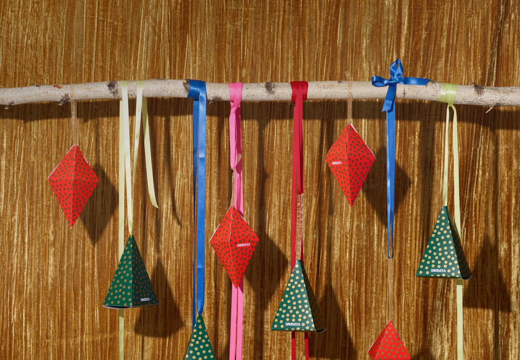 Boîtes vertes et rouges en forme de losange accrochées à une branche avec des rubans colorés.