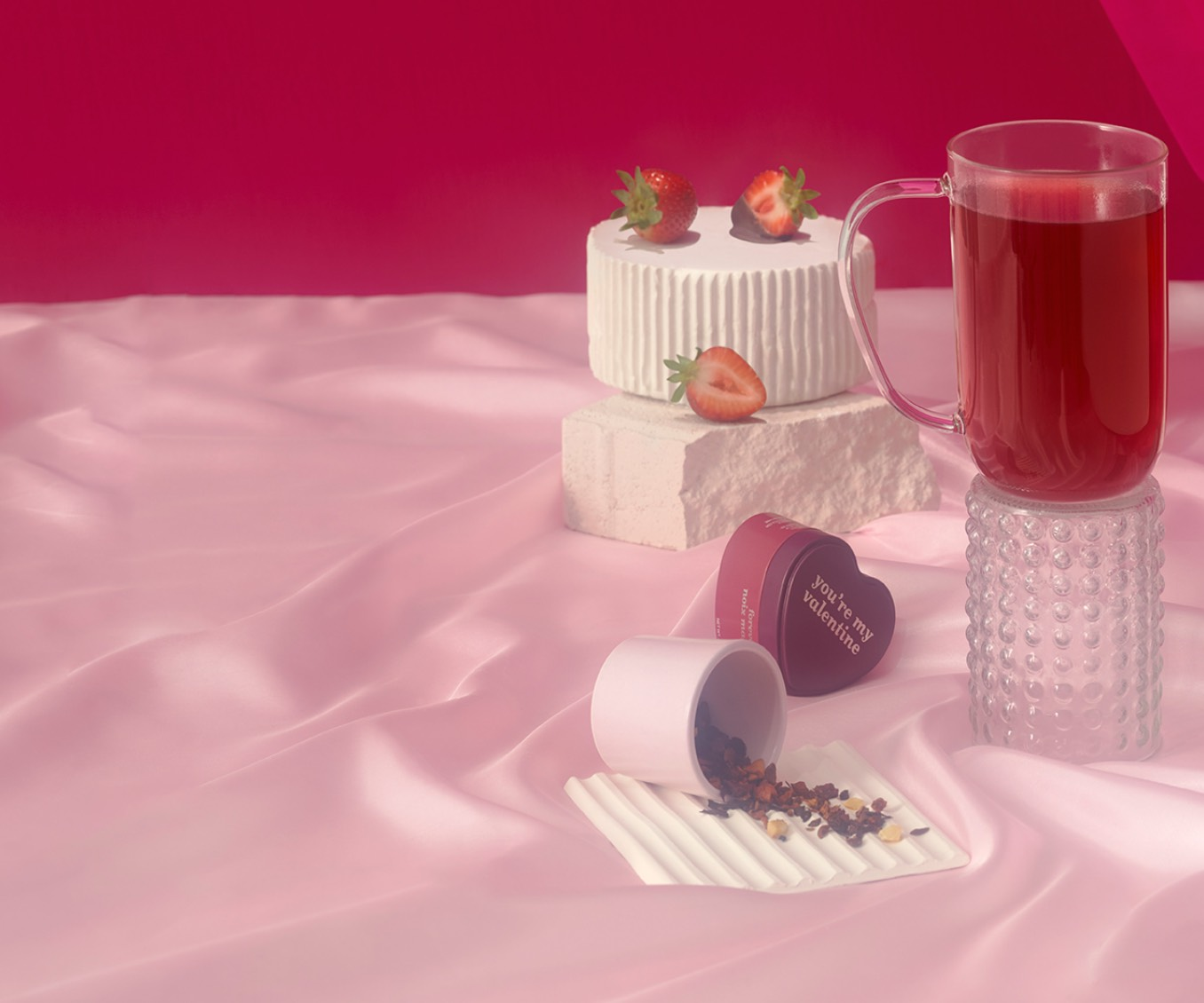 A Nordic mug filled with tea surrounded by strawberries and heart-shaped tins.