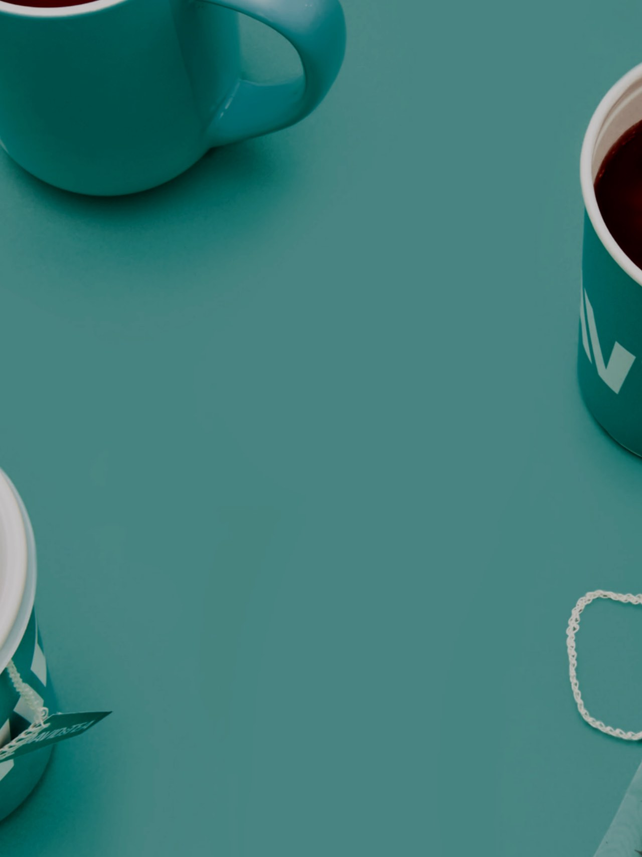 Two DAVIDsTEA to-go cups with tea and lid. Clear 16 oz glass mug with tea and sachet. Two 16 oz teal ceramic mugs with tea.