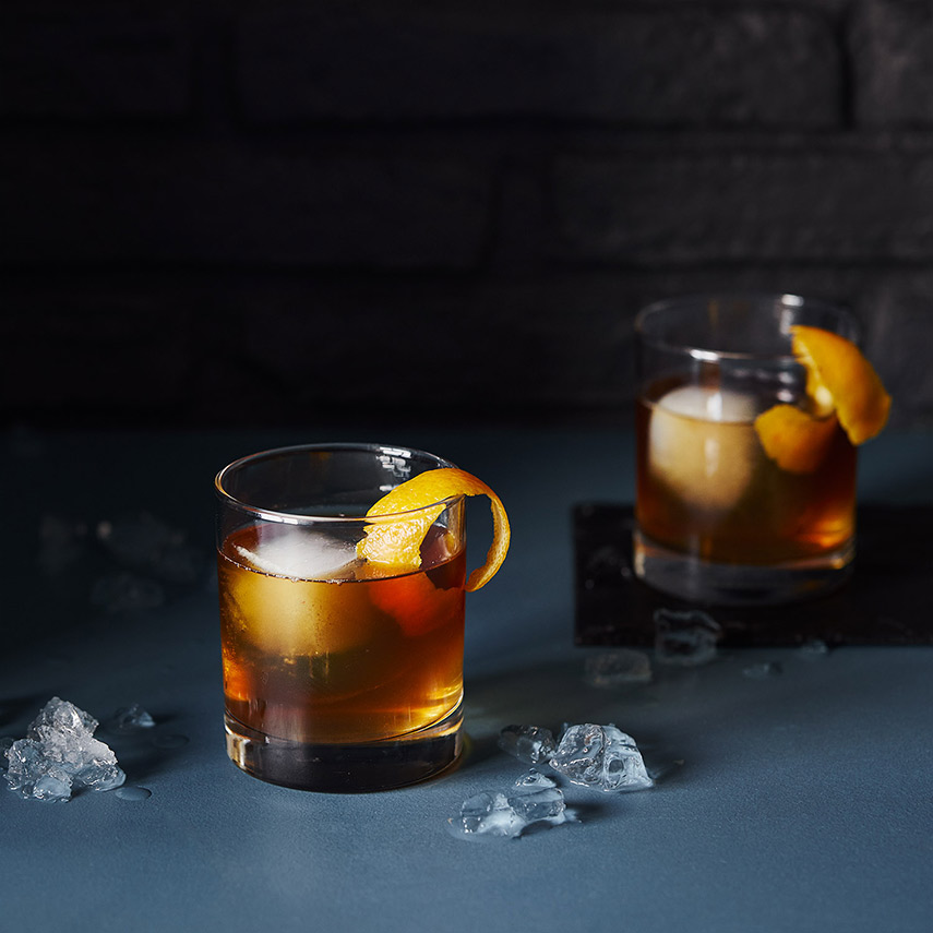 Two whisky glasses filled with a delicious mix of bourbon, chai tea, bitters, maple syrup and ice – topped with a curled orange rind.
