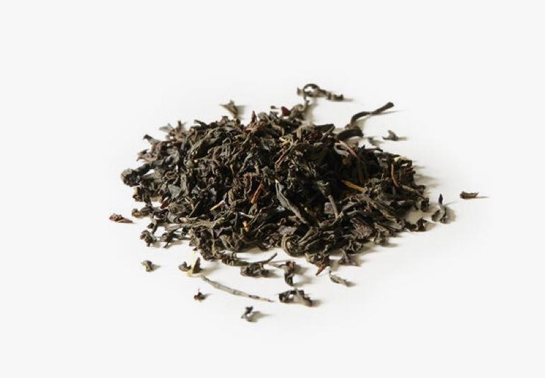 Des ingrédients du thé Earl Grey biologique, placés sur une surface blanche.