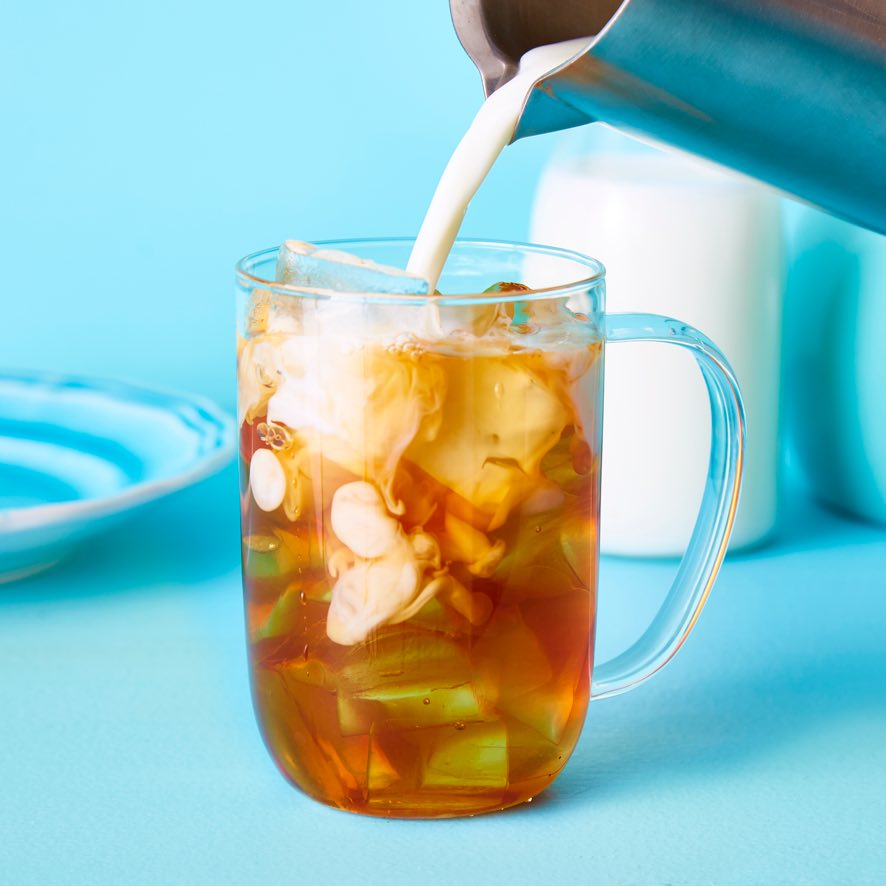 Milk pouring into clear 16 oz glass mug filled with ice and premium black tea.