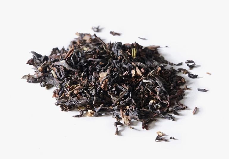 Des ingrédients du thé Darjeeling Happy Valley biologique, placés sur une surface blanche.