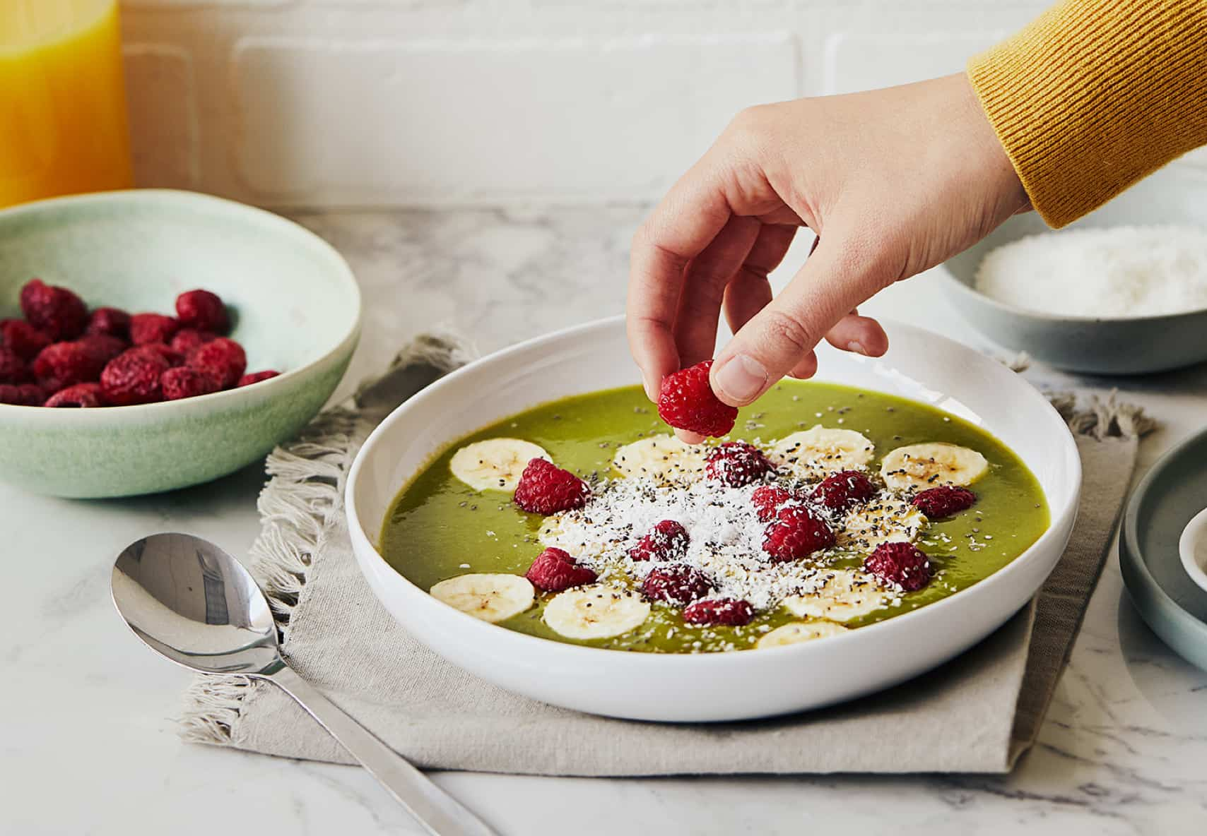 Hand adding raspberry to green matcha smoothie bowl with banana slices, raspberries and coconut flakes.