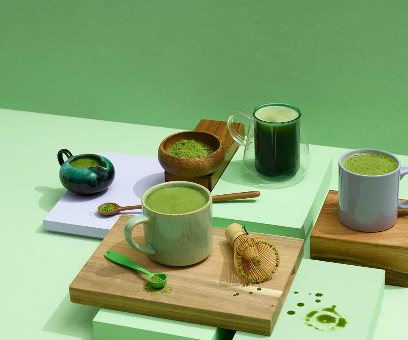 Assortment of 12 oz ceramic tea mugs filled with matcha tea, bamboo matcha whisk, bamboo spoon and bowl with matcha powder.
