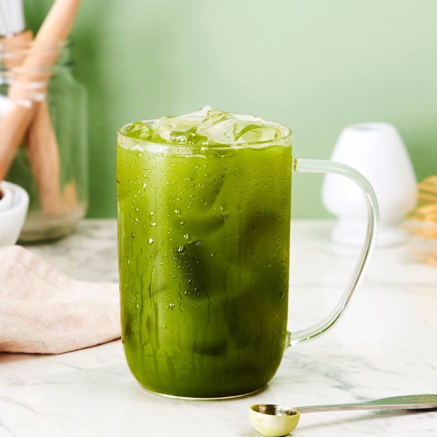 Clear 16 oz mug with matcha iced tea, stainless steel teaspoon to measure matcha green tea powder.