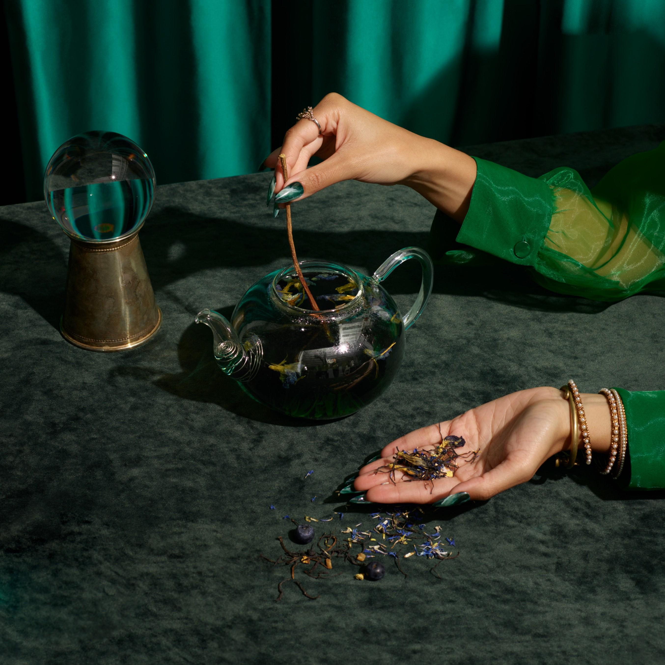 Main aux longs ongles mettant du thé en feuilles dans une théière de verre remplie d'un mélange de thé violet du Kenya chaud.