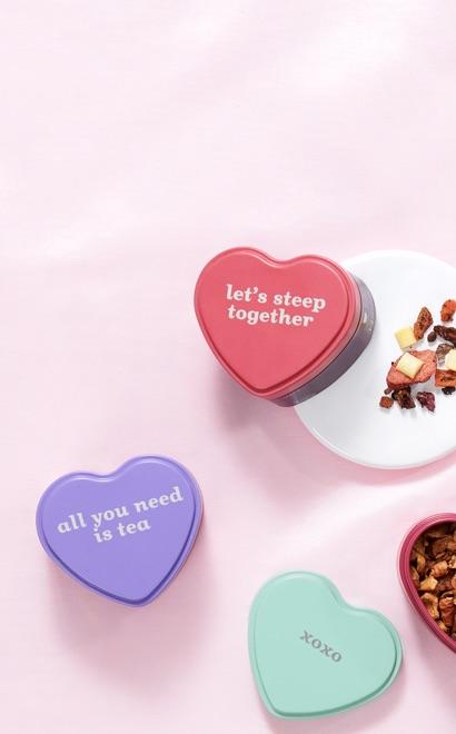 Trois boîtes de thé en forme de coeur sur un fond rose pâle.