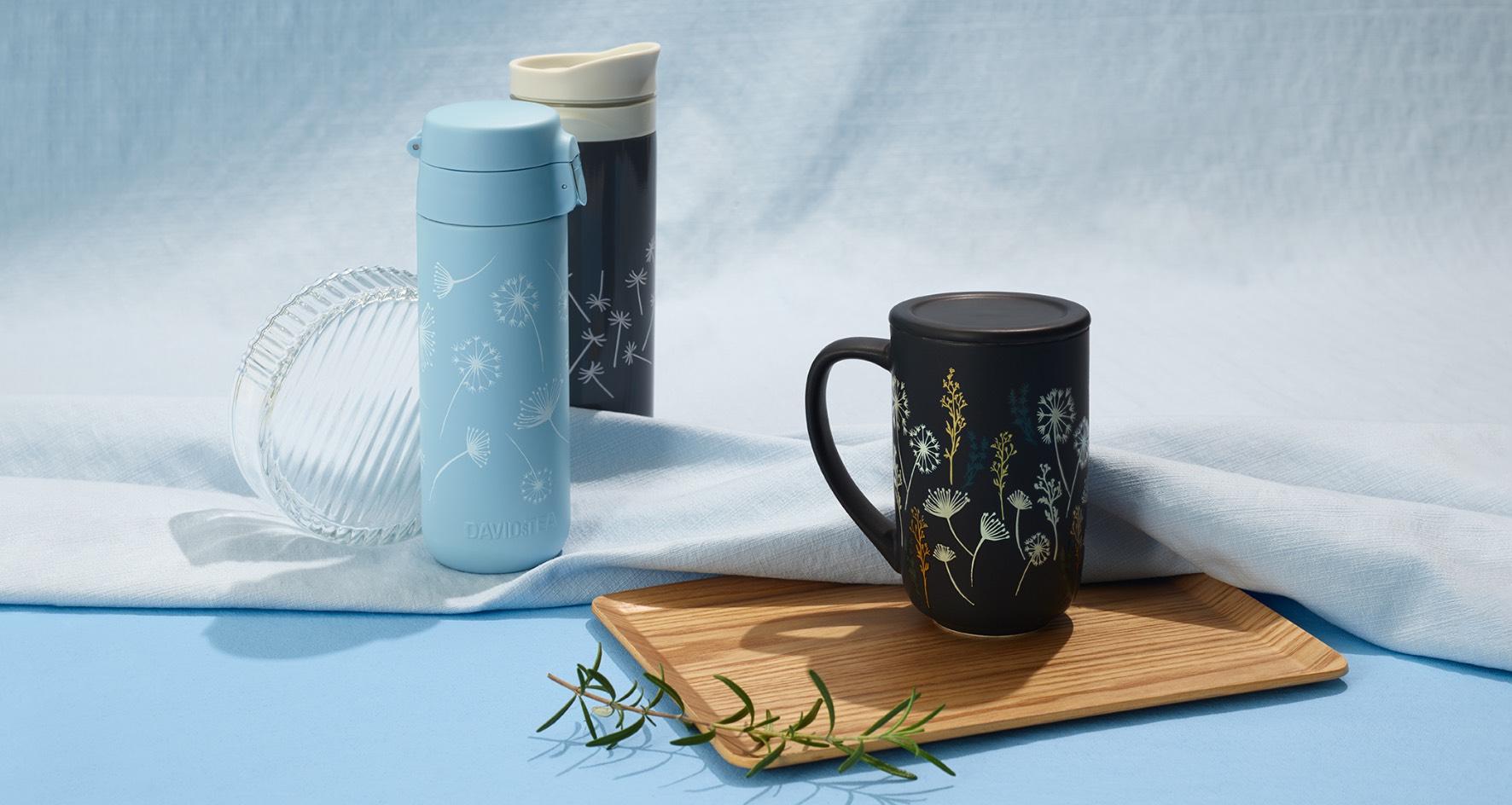 Tasse Nordic changeant de couleur noire à pissenlits et la Tasse de voyage à verrou à motif de pissenlits devant un fond bleu ciel.