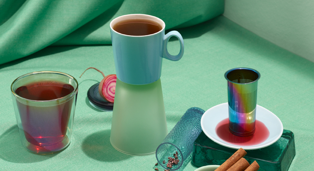 Various cups filled with teas on a turquoise surface with cinnamon sticks and a rainbow infuser.