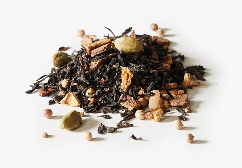 Des ingrédients du thé Pain doré à la cardamome, placés sur une surface blanche.