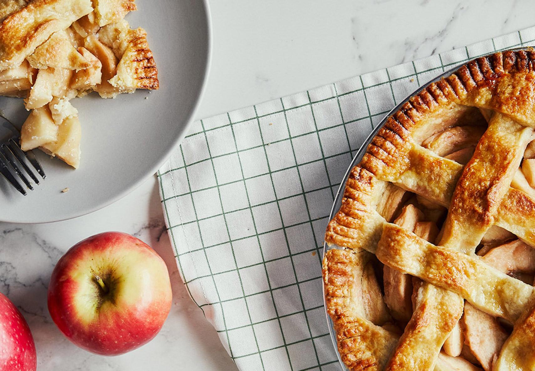 Plan supérieur d'une tarte aux pommes maison délicieuse avec un morceau découpé et une assiette représentant le morceau manquant et une fourchette.