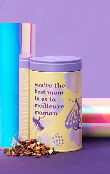 Un boîte pour la fête des Mères à côté d'un thé en feuilles.