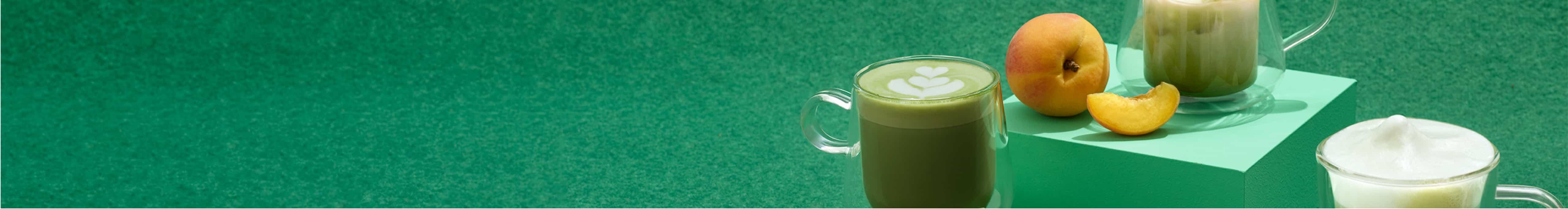 Tasses 12 oz en céramique remplies de thé matcha, fouet à matcha en bambou, cuillère en bambou et bol avec poudre de matcha.