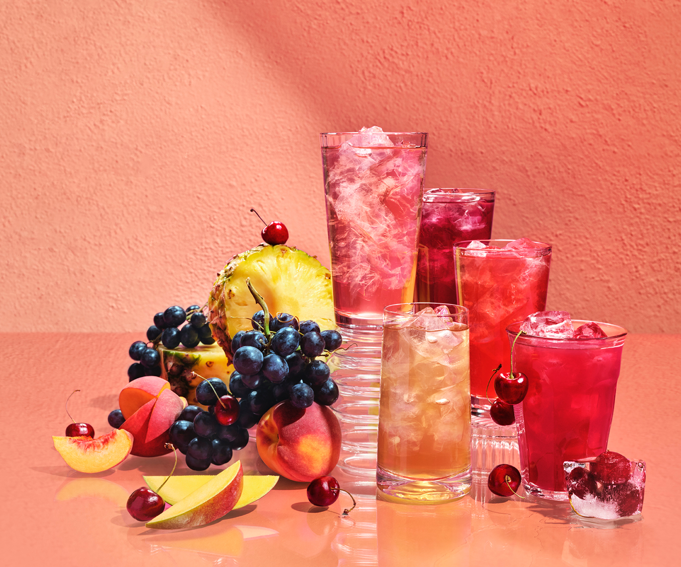 Various glasses filled with iced teas next to tropical fruits.