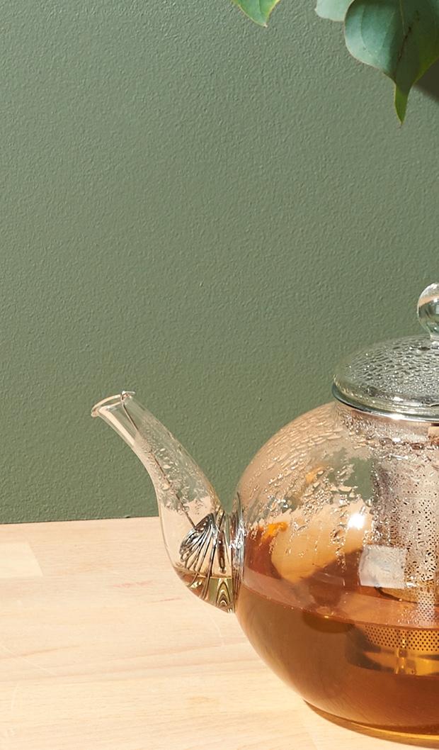 Pot à thé 28 oz en verre transparent rempli de thé vert chaud.