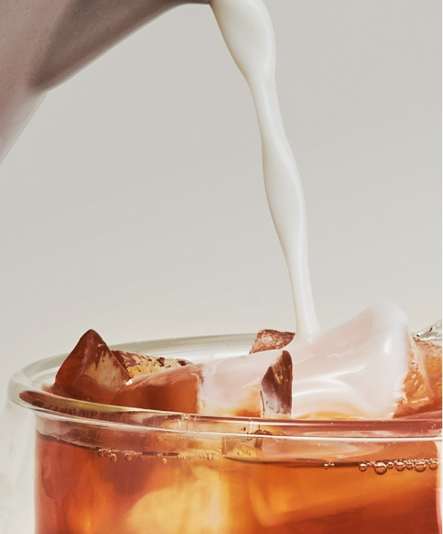 Milk being poured into an 18 oz double-walled glass mug filled with an iced latte made with black breakfast tea.