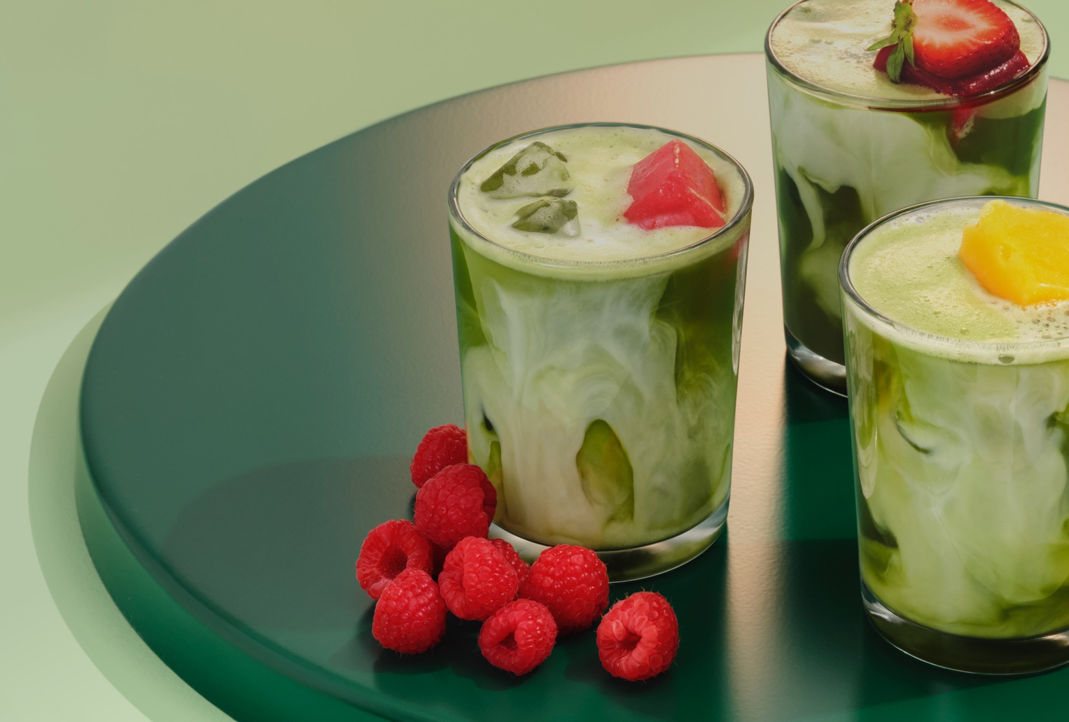 Three glasses filled with matcha placed on a circular tray with raspberries, mango and strawberries on top.
