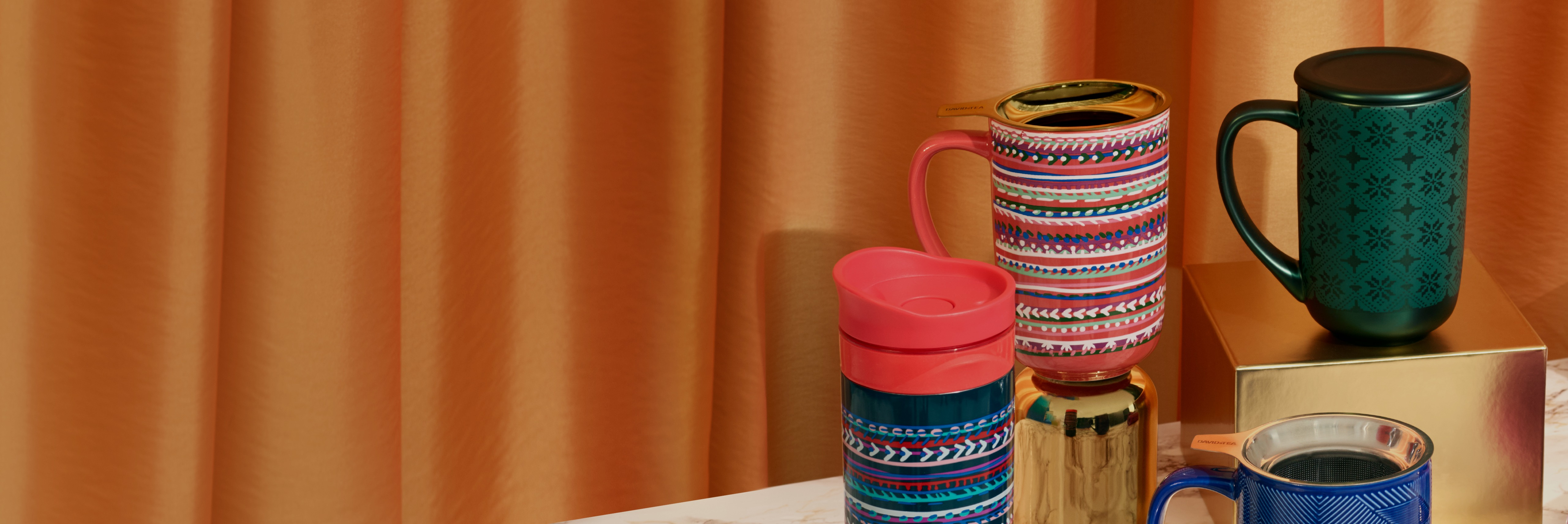 Four mugs (Nordic and travel mugs) placed on various gold boxes.